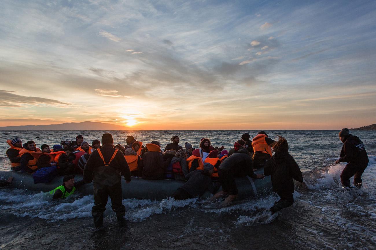 Vapaaehtoisten joukko ottaa venettä vastaan. Matkan viimeiset metrit ovat usein kohtalokkaita kivikkoisesta rannasta johtuen. Kuva: Sami Lensu